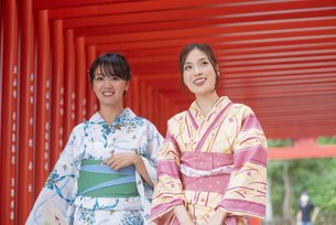 神社の鳥居をくぐる浴衣の女性神社2人の写真素材 [FYI04870707]