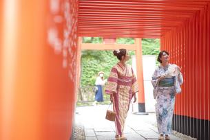 神社の鳥居をくぐる浴衣の女性神社2人の写真素材 [FYI04870708]