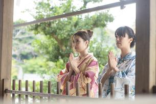 神社で合唱して祈願する浴衣の女性2人の写真素材 [FYI04870710]