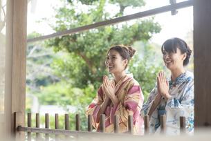 神社で合唱して祈願する浴衣の女性2人の写真素材 [FYI04870711]