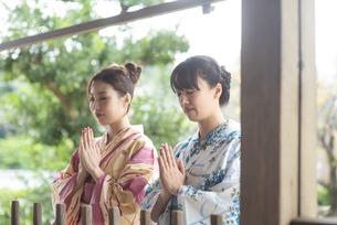 神社で合唱して祈願する浴衣の女性2人の写真素材 [FYI04870712]