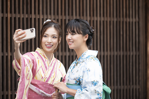 古民家を散歩して写真を撮る浴衣女性2人の写真素材 [FYI04870746]