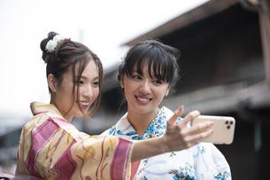 古民家を散歩して写真を撮る浴衣女性2人の写真素材 [FYI04870750]