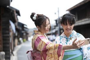 古民家を散歩して写真を撮る浴衣女性2人の写真素材 [FYI04870751]