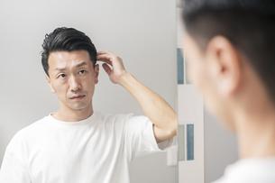 鏡を見て、肌の状態を確かめる男性の写真素材 [FYI04870918]