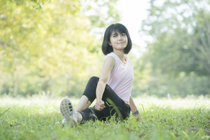 緑あふれる公園でストレッチをする若い女性の写真素材 [FYI04871013]