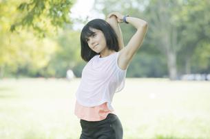 緑あふれる公園でストレッチをする若い女性の写真素材 [FYI04871018]