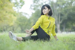 緑あふれる公園でストレッチをする若い女性の写真素材 [FYI04871029]