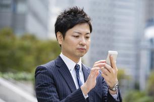 スマートフォンを使うビジネスマンの写真素材 [FYI04871037]