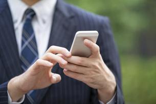 スマートフォンを使うビジネスマンの写真素材 [FYI04871041]