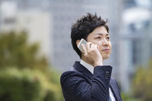 スマートフォンで会話するビジネスマンの写真素材 [FYI04871053]