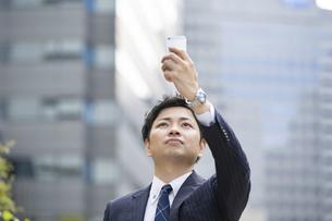 スマートフォンを使うビジネスマンの写真素材 [FYI04871072]