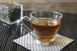 ガラスキューブ容器に入れたウーロン茶葉と一杯のウーロン茶の写真素材 [FYI04871245]