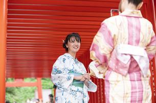 神社の鳥居で写真を撮る浴衣の女性神社2人の写真素材 [FYI04871458]
