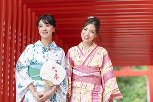 神社の鳥居をくぐる浴衣の女性神社2人の写真素材 [FYI04871459]