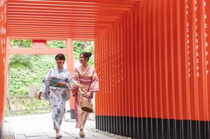 神社の鳥居をくぐる浴衣の女性神社2人の写真素材 [FYI04871460]