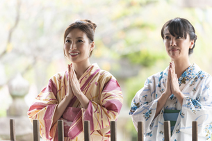 神社で合唱して祈願する浴衣の女性2人の写真素材 [FYI04871467]