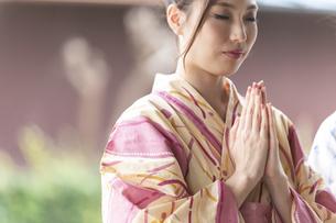 神社で合唱して祈願する浴衣の女性の写真素材 [FYI04871468]