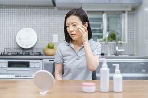 不安な表情で肌の状態を確かめる中年女性の写真素材 [FYI04871472]