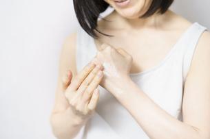 手の甲にクリームを塗る女性の写真素材 [FYI04871477]