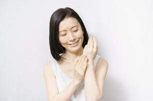 手の甲にクリームを塗る女性の写真素材 [FYI04871478]