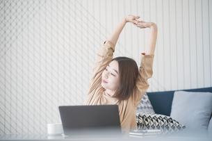 カジュアルな空間での仕事中のストレッチする女性の写真素材 [FYI04871496]