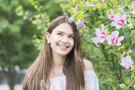 リラックスした表情で緑地を散歩する若い女性の写真素材 [FYI04871511]