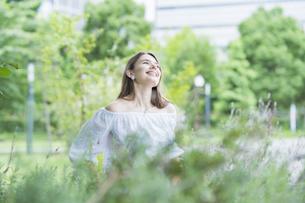 リラックスした表情で緑地を散歩する若い女性の写真素材 [FYI04871514]