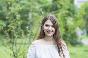 リラックスした表情で緑地を散歩する若い女性の写真素材 [FYI04871517]