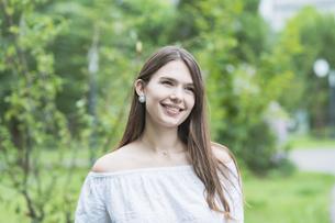 リラックスした表情で緑地を散歩する若い女性の写真素材 [FYI04871518]