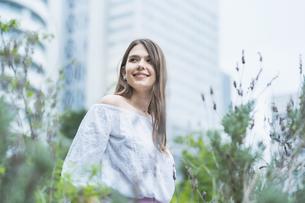 リラックスした表情で緑地を散歩する若い女性の写真素材 [FYI04871519]