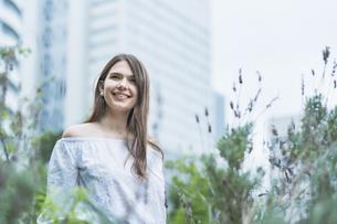 リラックスした表情で緑地を散歩する若い女性の写真素材 [FYI04871520]