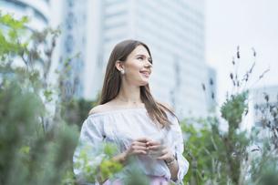 リラックスした表情で緑地を散歩する若い女性の写真素材 [FYI04871521]