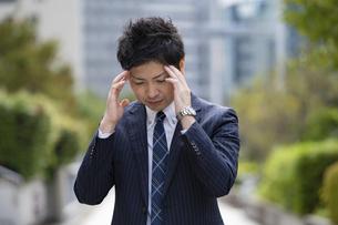 頭痛に悩むビジネスマンの写真素材 [FYI04871612]