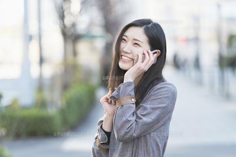 笑顔で電話する女性の写真素材 [FYI04871614]