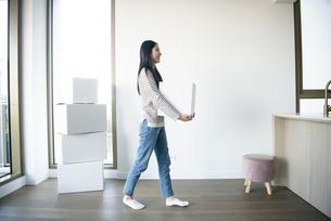 引越しの段ボールを運んでいる女性の写真素材 [FYI04871788]