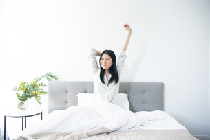 ベッドでストレッチをしている女性の写真素材 [FYI04871798]