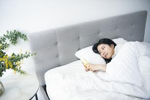 ベッドの中でスマホを触っている女性の写真素材 [FYI04871860]