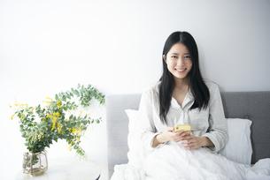 ベッドでスマホを持っている女性の写真素材 [FYI04871862]