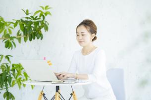 明るい部屋でノートパソコンを操作する女性の写真素材 [FYI04872575]