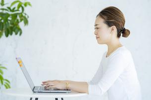 明るい部屋でノートパソコンを操作する女性の写真素材 [FYI04872578]