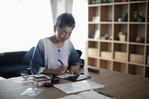 タブレットPCを見ながら葉書を書く日本人シニア女性の写真素材 [FYI04873011]