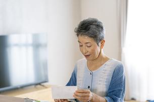葉書を書く日本人シニア女性の写真素材 [FYI04873043]