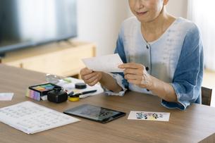 タブレットPCを見ながら葉書を書く日本人シニア女性の写真素材 [FYI04873044]