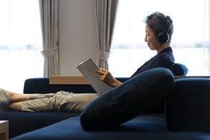 ヘッドホンをつけて読書をする日本人シニア女性の写真素材 [FYI04873047]