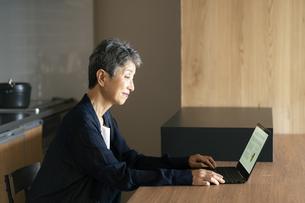 ノートパソコンを操作する日本人シニア女性の写真素材 [FYI04873150]
