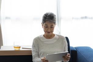 タブレットPCを見る日本人シニア女性の写真素材 [FYI04873163]