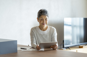 タブレットPCを見る日本人シニア女性の写真素材 [FYI04873165]