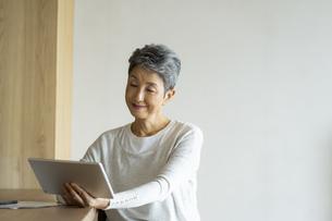 タブレットPCを見る日本人シニア女性の写真素材 [FYI04873167]
