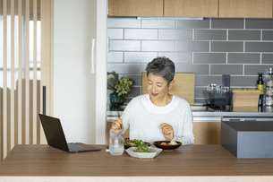ノートパソコンを見ながら食事をする日本人シニア女性の写真素材 [FYI04873168]